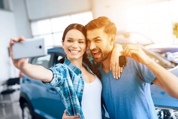 Un hombre y una mujer hacen selfie cerca de su auto nuevo.