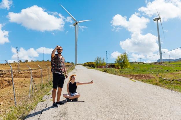 Hombre y mujer haciendo autostop en la carretera