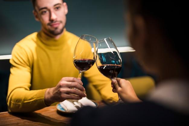 Hombre y mujer haciendo copas de vino y sentados a la mesa