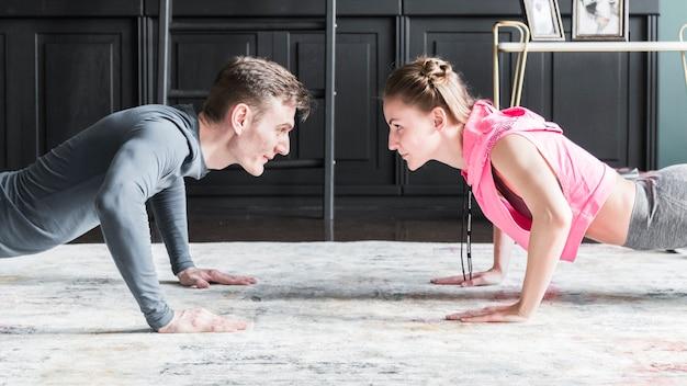 Hombre y mujer haciendo flexiones