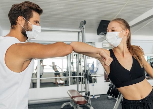 Hombre y mujer haciendo el saludo del codo en el gimnasio