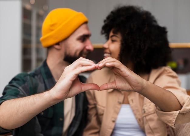 Hombre y mujer haciendo señal de hogar con sus manos