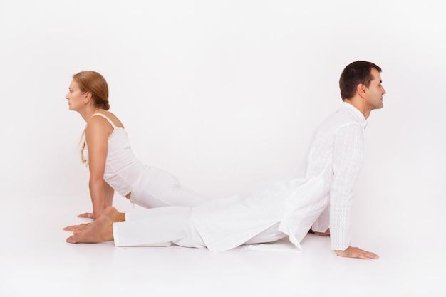 Hombre y mujer haciendo yoga. clase de yoga combinada con el entrenador.