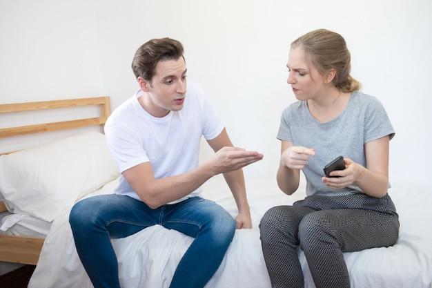 El hombre y la mujer infelices caucásicos tienen argumento sobre el teléfono móvil inteligente en el hogar, el concepto de problema social de relación con espacio de copia.