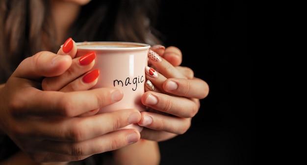 Hombre y mujer irreconocibles sostienen con dos manos una taza de café caliente.