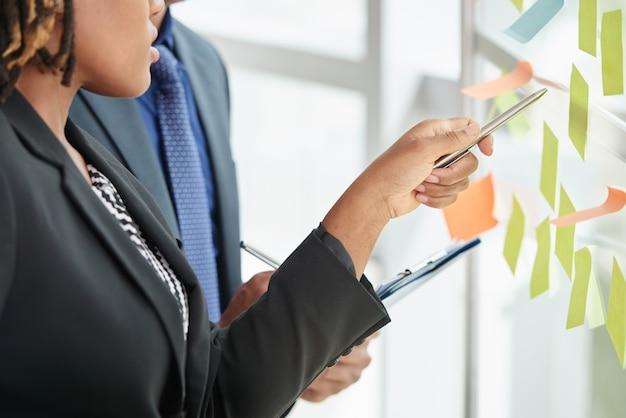 Hombre y mujer irreconocibles en trajes de negocios mirando notas adhesivas en la ventana