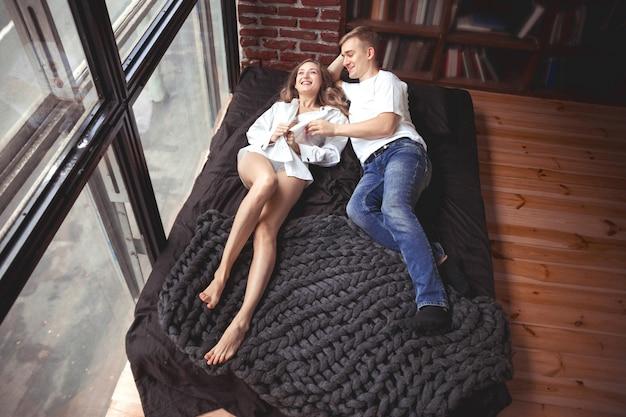 Hombre y mujer joven se acuestan en la cama y se divierten
