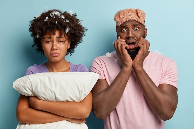 Hombre y mujer joven con antifaz para dormir y almohada