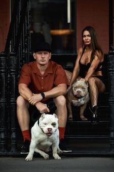 Hombre y mujer joven elegantemente vestidos con una figura atlética con dos perros matones americanos debajo del puente en las calles de la ciudad