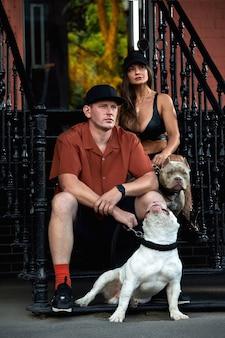Hombre y mujer joven elegantemente vestidos con una figura atlética con dos perros matones americanos sentados en los escalones de las calles de la ciudad