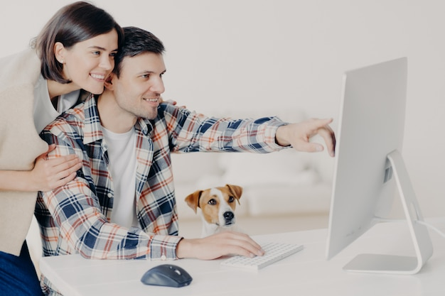 El hombre y la mujer joven feliz positiva trabajan remotamente en la computadora, pasan tiempo juntos, indican en el monitor, hacen reservas en línea, buscan información sobre hoteles, hacen planes para futuros viajes