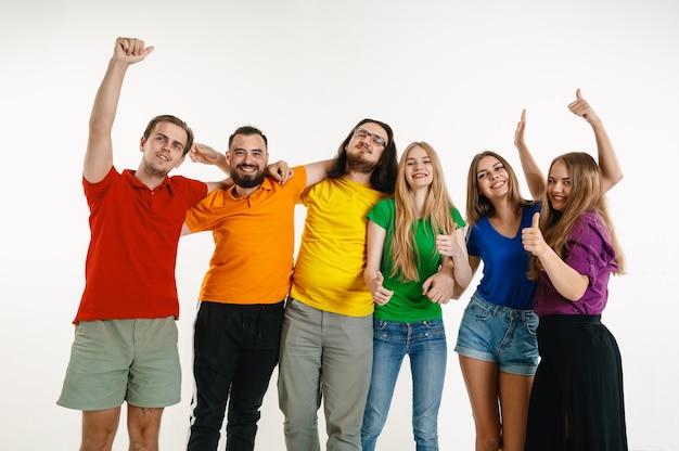 El hombre y la mujer joven lucieron en colores de la bandera lgbt en la pared blanca