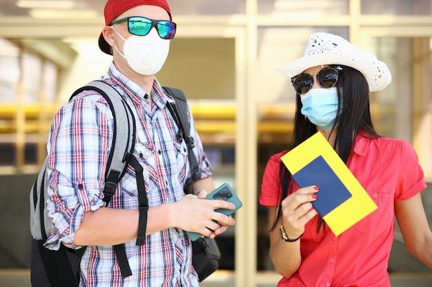 Hombre y mujer joven con pasaporte y boleto en mano están esperando el vuelo