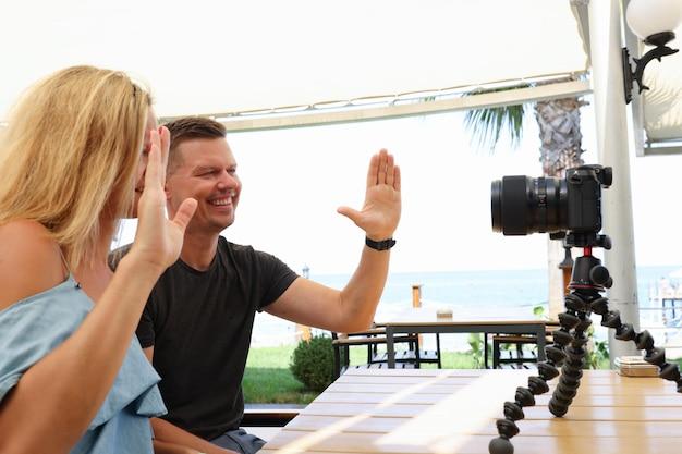 Hombre y mujer joven sentados en el café en la calle y agitando la mano ante las ganancias familiares de la cámara