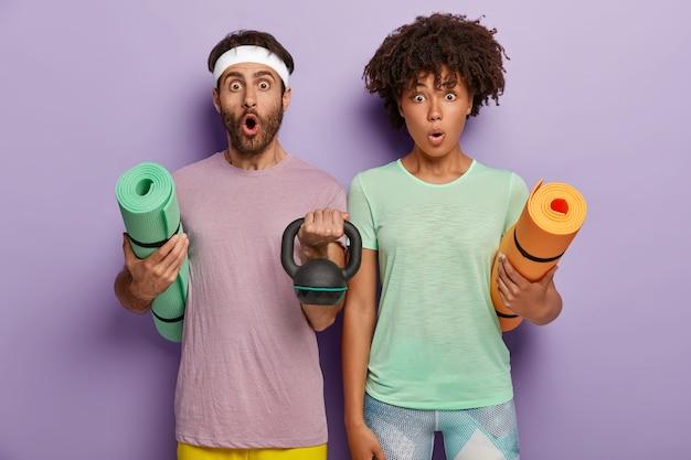 Hombre y mujer joven sorprendidos llevan karemats, levantan peso, vestidos con ropa deportiva
