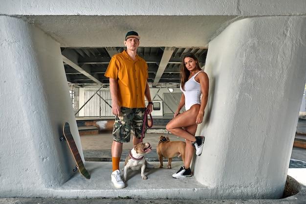 Hombre y mujer jóvenes elegantemente vestidos con una figura atlética con dos perros matones americanos debajo del puente en las calles de la ciudad.