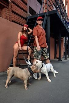 Hombre y mujer jóvenes elegantemente vestidos con una figura atlética con dos perros matones americanos sentados en los escalones de las calles de la ciudad.