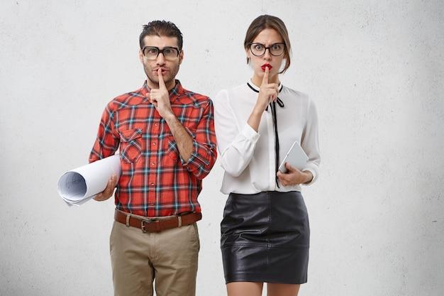 El hombre y la mujer jóvenes enojados usan anteojos grandes, ropa formal, muestran signos de silencio como trabajo en un proyecto serio