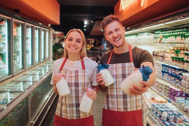 El hombre y la mujer jóvenes están parados en la tienda de comestibles y el estante de productos lácteos. sostienen botellas de vidrio con leche y posan ante la cámara. trabajadores felices positivos sonriendo.