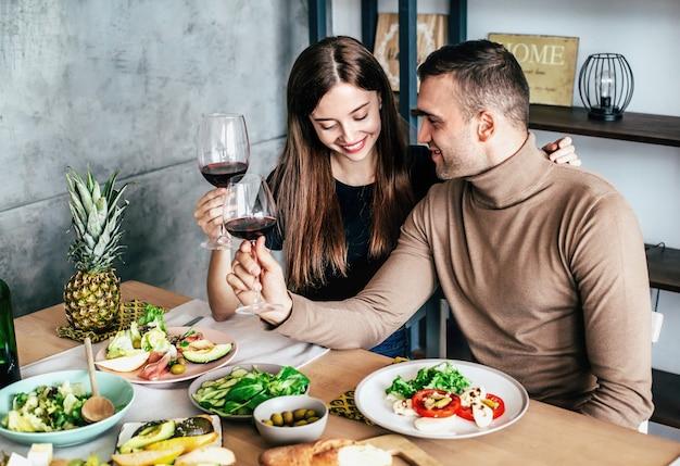 El hombre y la mujer jóvenes están sentados en una mesa cubierta con comida y bebidas con vasos de vino en sus manos