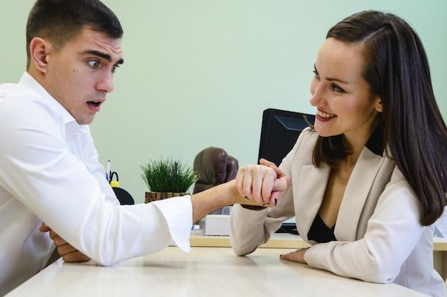 El hombre y la mujer jóvenes luchan en sus manos en el escritorio en la oficina por un lugar jefe, cabeza