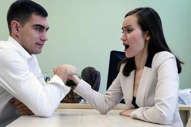 Hombre y mujer jóvenes luchan en sus manos en el escritorio en la oficina por un lugar jefe