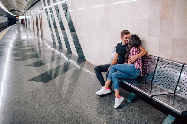 El hombre y la mujer jóvenes usan bajo tierra. pareja en metro encantadora joven y mujer se sientan juntos. la abraza y besa. amor a primera vista. vista urbana