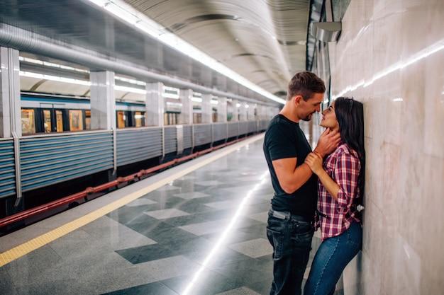 El hombre y la mujer jóvenes usan bajo tierra. pareja en metro la gente alegre y paasionada se inclina hacia la pared. tiempo de besos guy toma la mano de su cuello. historia de amor. vista urbana moderna.