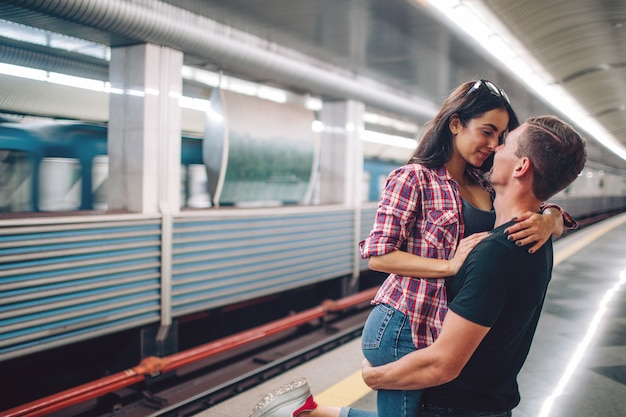 El hombre y la mujer jóvenes usan bajo tierra. pareja en metro historia de amor. joven sostenga a mujer en manos y beso. amor a primera vista. vista urbana moderna.