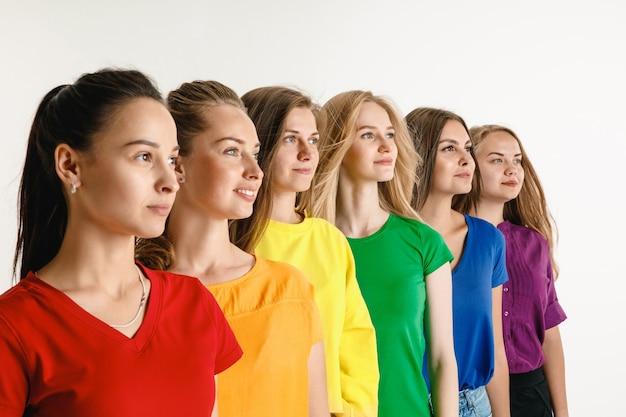 El hombre y la mujer jóvenes vestían los colores de la bandera lgbt en la pared blanca. modelos con camisas brillantes