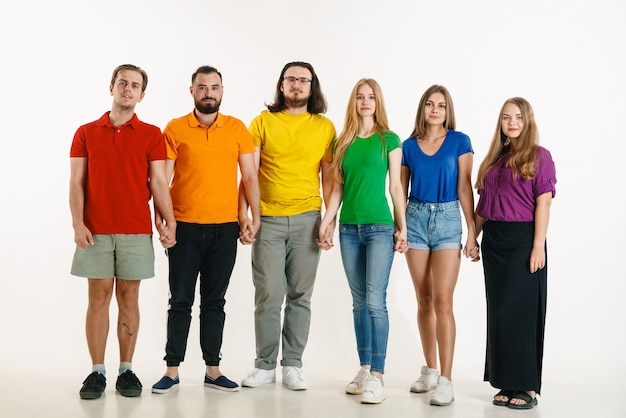 El hombre y la mujer jóvenes vestían los colores de la bandera lgbt sobre fondo blanco. modelos caucásicos con camisas brillantes.