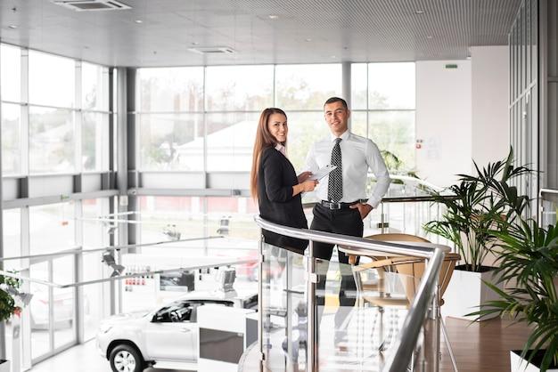 Hombre y mujer juntos en concesionario de automóviles