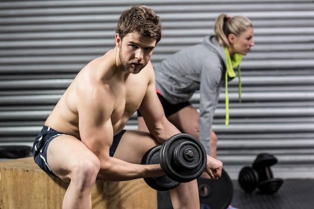 Hombre y mujer levantando pesas en el gimnasio de crossfit