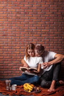 Hombre y mujer leyendo juntos un libro