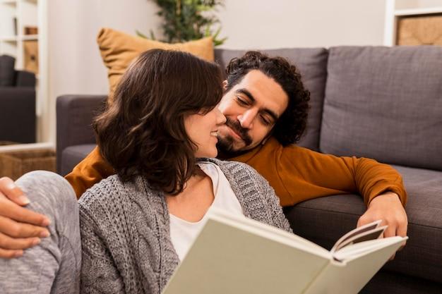 Hombre y mujer leyendo juntos en la sala de estar