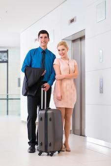 Hombre y mujer llegando al lobby del hotel con maleta