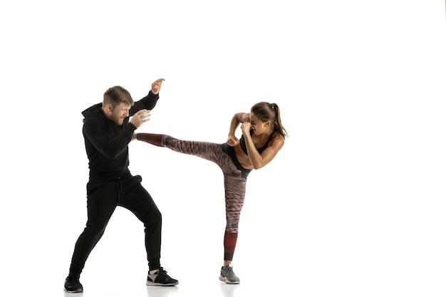 Hombre y mujer luchando en blanco, concepto de autodefensa de las mujeres