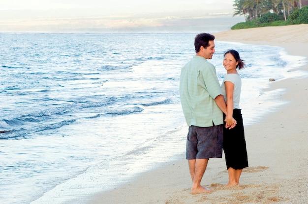 Hombre y mujer de la mano en la playa