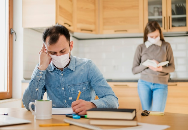 Hombre y mujer con máscaras médicas aprendiendo desde casa