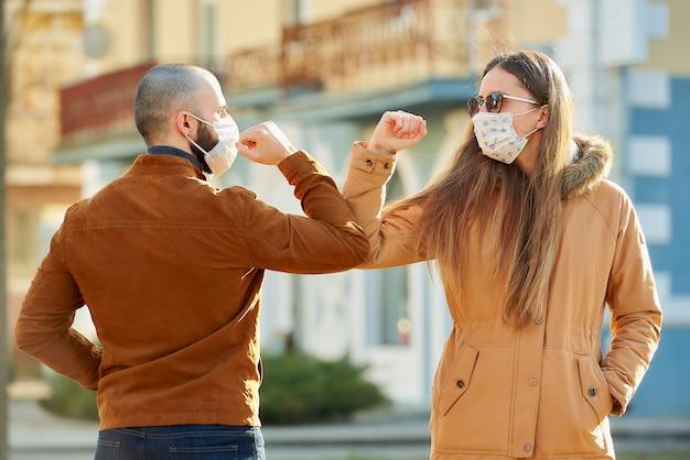 Un hombre y una mujer con máscaras médicas se encuentran en la calle con las manos desnudas.