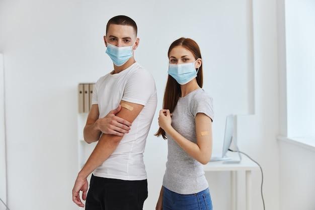 Hombre y mujer con máscaras médicas en la inmunidad sanitaria del pasaporte de la vacuna del hospital