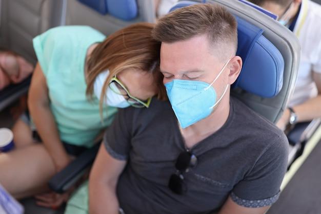 El hombre y la mujer con máscaras protectoras médicas duermen en la cabina del avión