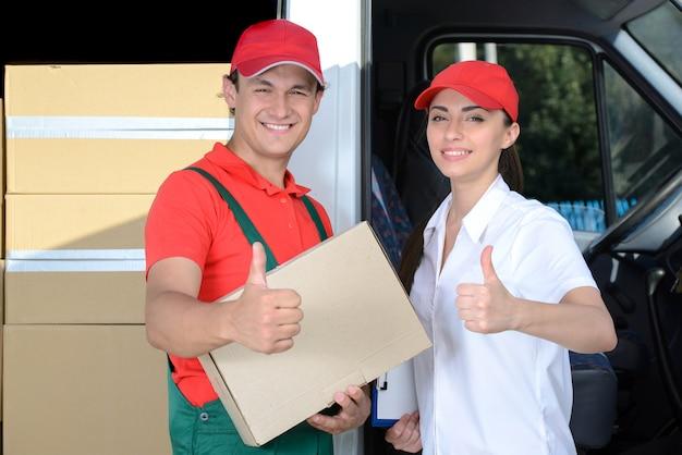 Hombre y mujer mensajero de entrega postal hombre antes de la furgoneta de carga