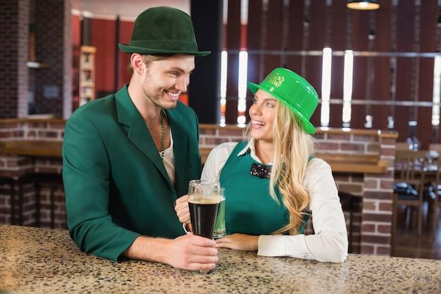 Hombre y mujer mirando el uno al otro mientras sostiene cervezas