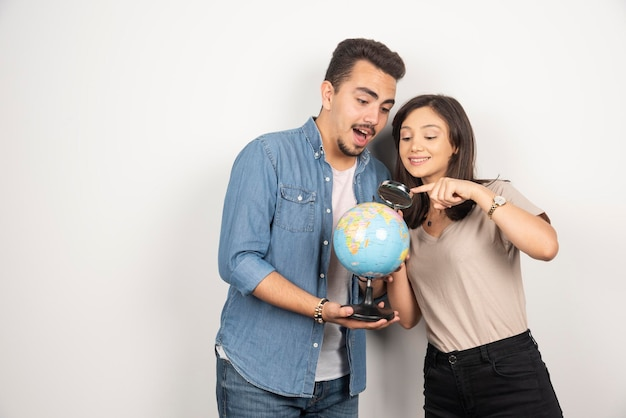 Hombre y mujer mirando globo en blanco.