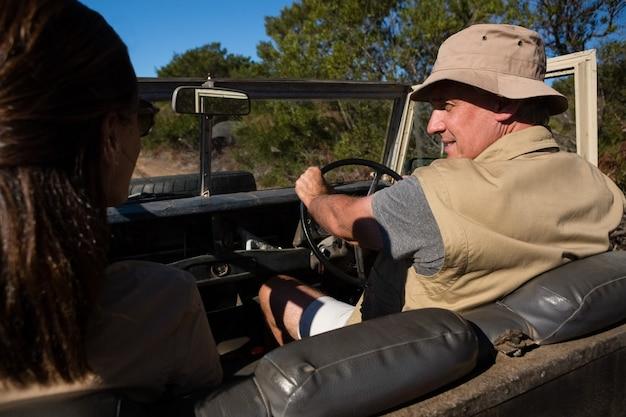 Hombre con mujer mirando a otro lado mientras conduce vehículo