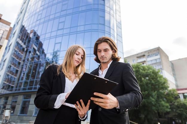 Hombre y mujer mirando un portapapeles