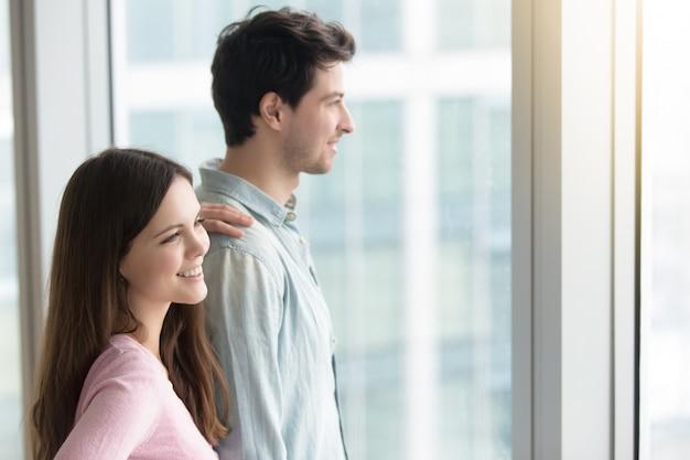 Hombre y mujer mirando por la ventana al paisaje de la ciudad