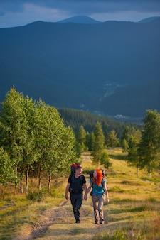 Hombre y mujer con mochilas trepando por una hermosa zona montañosa