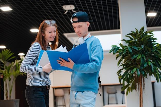 El hombre y la mujer de moda moderna joven discuten un proyecto conjunto en la oficina